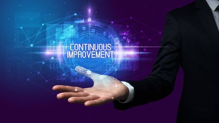 Man hand holding CONTINUOUS IMPROVEMENT inscription, technology concept