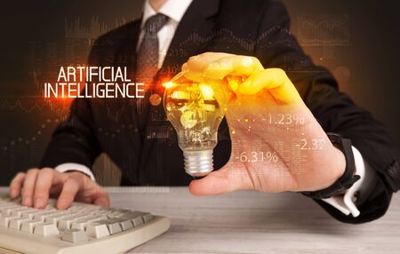 Businessman holding lightbulb with ARTIFICIAL INTELLIGENCE inscription, Business technology concept Stock Photo