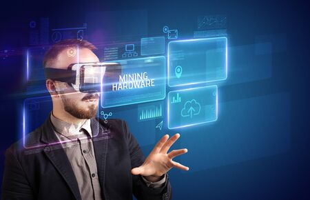 Businessman looking through Virtual Reality glasses with MINING HARDWARE inscription, new technology concept