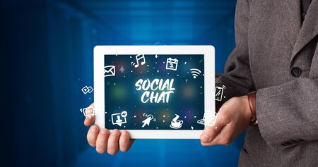 Young business person working on tablet and shows the inscription: SOCIAL CHAT Stockfoto