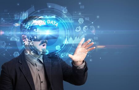 Businessman looking through Virtual Reality glasses with BIG DATA inscription, innovative technology concept Stock Photo