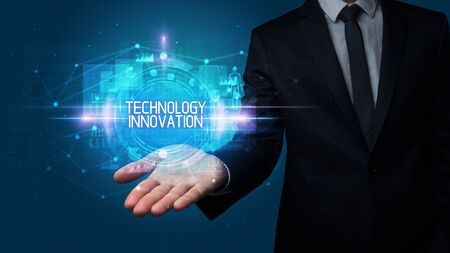 Man hand holding TECHNOLOGY INNOVATION inscription, technology concept Stock Photo