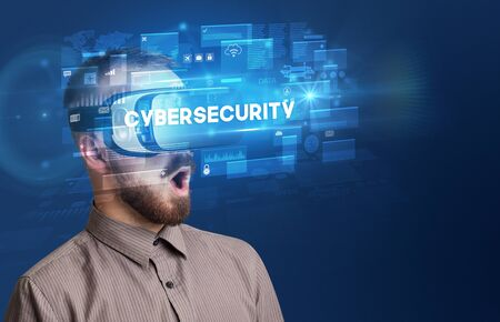 Businessman looking through Virtual Reality glasses with CYBERSECURITY inscription, innovative security concept