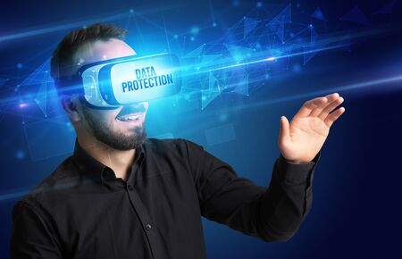 Businessman looking through Virtual Reality glasses with DATA PROTECTION inscription, cyber security concept Foto de archivo
