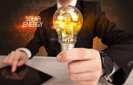 Businessman holding lightbulb with SOLAR ENERGY inscription, Business technology concept
