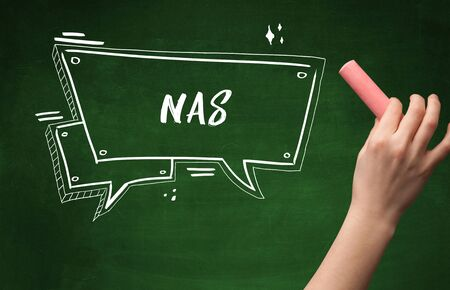 Hand drawing NAS abbreviation with white chalk on blackboard