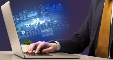 Businessman working on laptop with EDGE COMPUTING inscription, cyber technology concept