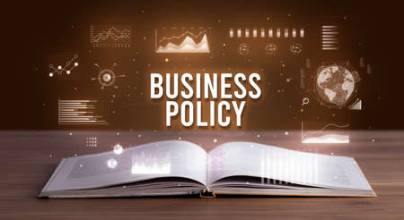 BUSINESS POLICY inscription coming out from an open book, creative business concept Foto de archivo