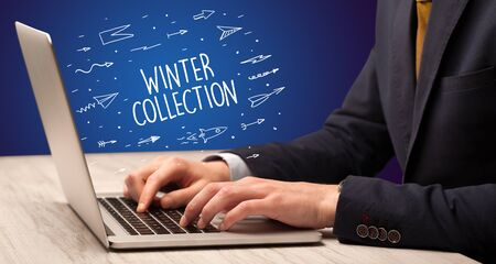 Businessman working on laptop with WINTER COLLECTION inscription, online shopping concept 版權商用圖片