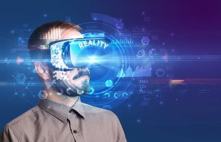 Businessman looking through Virtual Reality glasses with REALITY inscription, innovative technology concept