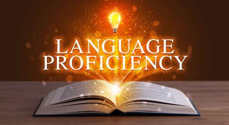 LANGUAGE PROFICIENCY inscription coming out from an open book, educational concept Foto de archivo