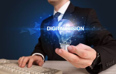 Businessman holding light bulb with DIGITAL VISION inscription, innovative technology concept