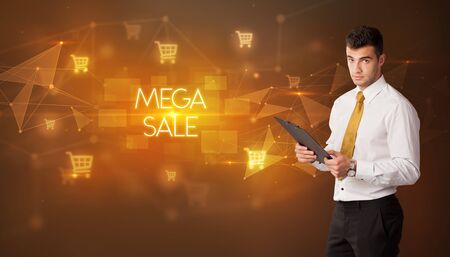 Businessman with shopping cart icons and MEGA SALE inscription, online shopping concept 版權商用圖片