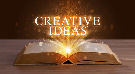 CREATIVE IDEAS inscription coming out from an open book, educational concept Foto de archivo