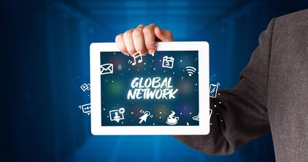 Young business person working on tablet and shows the inscription: GLOBAL NETWORK Stockfoto