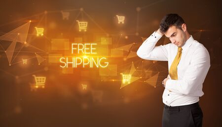 Businessman with shopping cart icons and FREE SHIPPING inscription, online shopping concept 版權商用圖片
