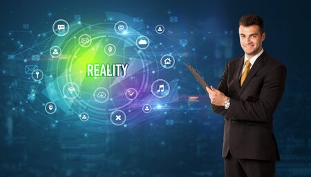 Businessman thinking in front of technology related icons and REALITY inscription, modern technology concept
