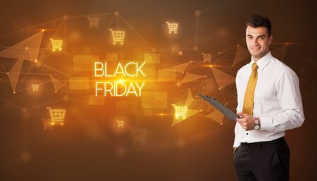 Businessman with shopping cart icons and BLACK FRIDAY inscription, online shopping concept
