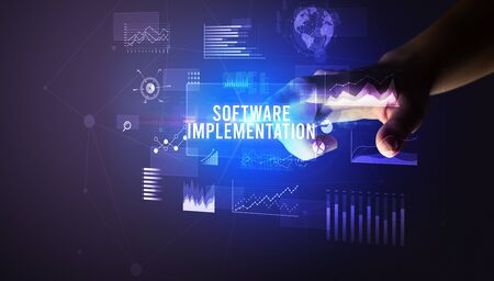 Hand touching SOFTWARE IMPLEMENTATION inscription, new business technology concept