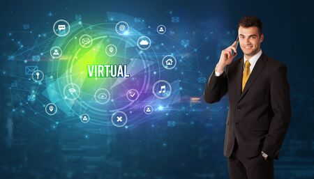 Businessman thinking in front of technology related icons and VIRTUAL inscription, modern technology concept