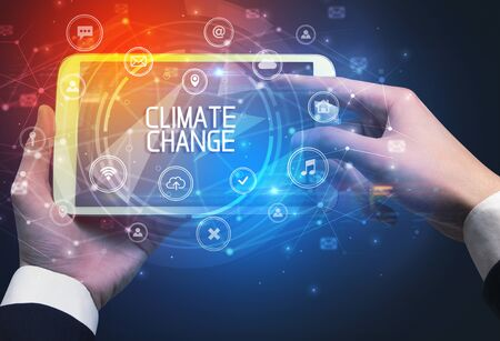 Close-up of a tablet with CLIMATE CHANGE inscription, innovative technology concept 版權商用圖片