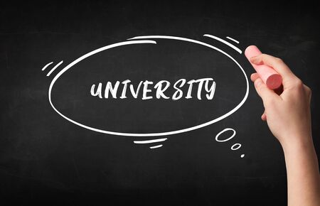 Hand drawing UNIVERSITY inscription with white chalk on blackboard, education concept