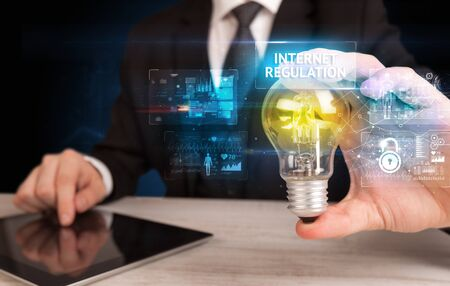 Businessman holding lightbulb with INTERNET REGULATION inscription, online security idea concept