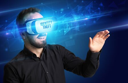 Businessman looking through Virtual Reality glasses with IDENTITY THEFT inscription, cyber security concept 版權商用圖片