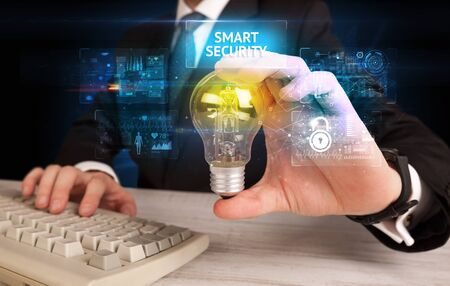 Businessman holding lightbulb with SMART SECURITY inscription, online security idea concept