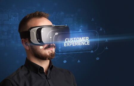 Businessman looking through Virtual Reality glasses with CUSTOMER EXPERIENCE inscription, social networking concept