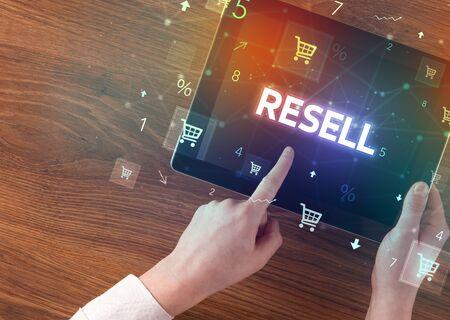 Gros plan d'une main tenant une tablette avec inscription REVENDRE, concept d'achat en ligne