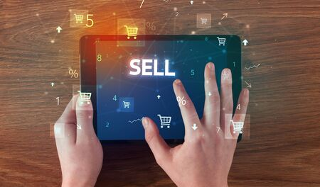 Close-up of a hand holding tablet with SELL inscription, online shopping concept
