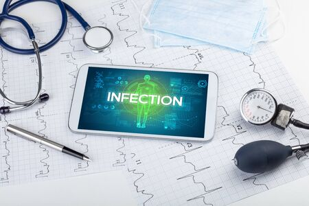 Tablet pc and doctor tools with INFECTION inscription, coronavirus concept Stock Photo