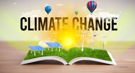 Open book with CLIMATE CHANGE  inscription, renewable energy concept