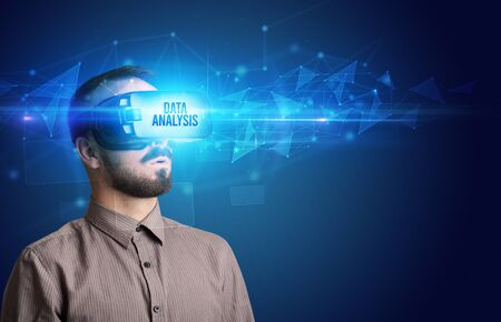 Businessman looking through Virtual Reality glasses with DATA ANALYSIS inscription, cyber security concept