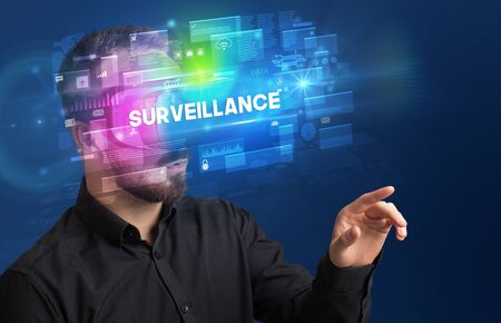 Businessman looking through Virtual Reality glasses with SURVEILLANCE inscription, innovative security concept 版權商用圖片