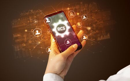 Female hand holding smartphone with RCS abbreviation, modern technology concept