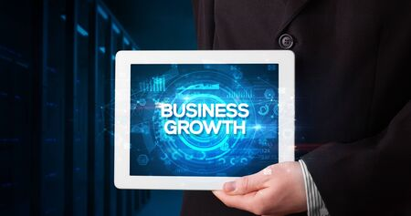 Young business person working on tablet and shows the inscription: BUSINESS GROWTH, business concept Stock Photo