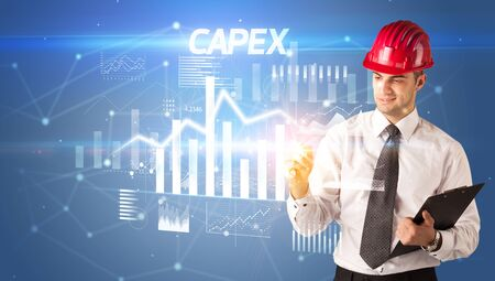 Handsome businessman with helmet drawing CAPEX inscription, architecture business plan concept