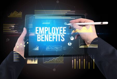 Close-up of hands holding tablet with EMPLOYEE BENEFITS inscription, modern business concept