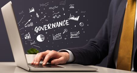 Businessman working on laptop with GOVERNANCE inscription, modern business concept