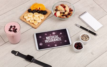 MEDICAL INSURANCE concept in tablet pc with healthy food around, top view