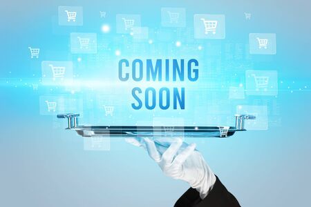 Waiter serving COMING SOON inscription, online shopping concept 免版税图像