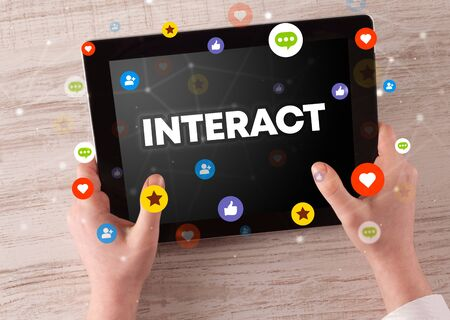 Close-up of a touchscreen with INTERACT inscription, social networking concept 免版税图像