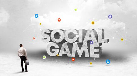 Young businessman standing in front of SOCIAL GAME inscription, social media concept