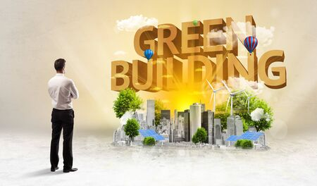 Rear view of a businessman standing in front of GREEN BUILDING inscription, Environmental protection concept