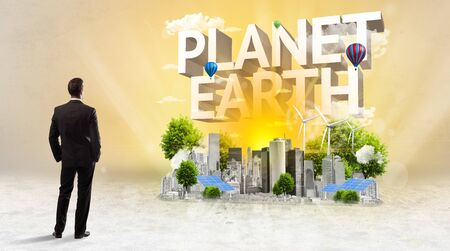 Rear view of a businessman standing in front of PLANET EARTH inscription, Environmental protection concept