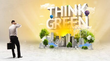 Rear view of a businessman standing in front of THINK GREEN inscription, Environmental protection concept