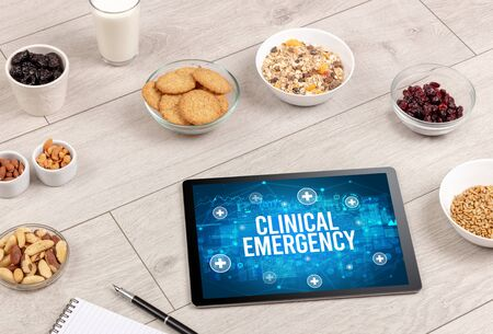 CLINICAL EMERGENCY concept in tablet pc with healthy food around, top view