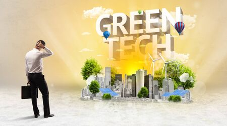 Rear view of a businessman standing in front of GREEN TECH inscription, Environmental protection concept Фото со стока